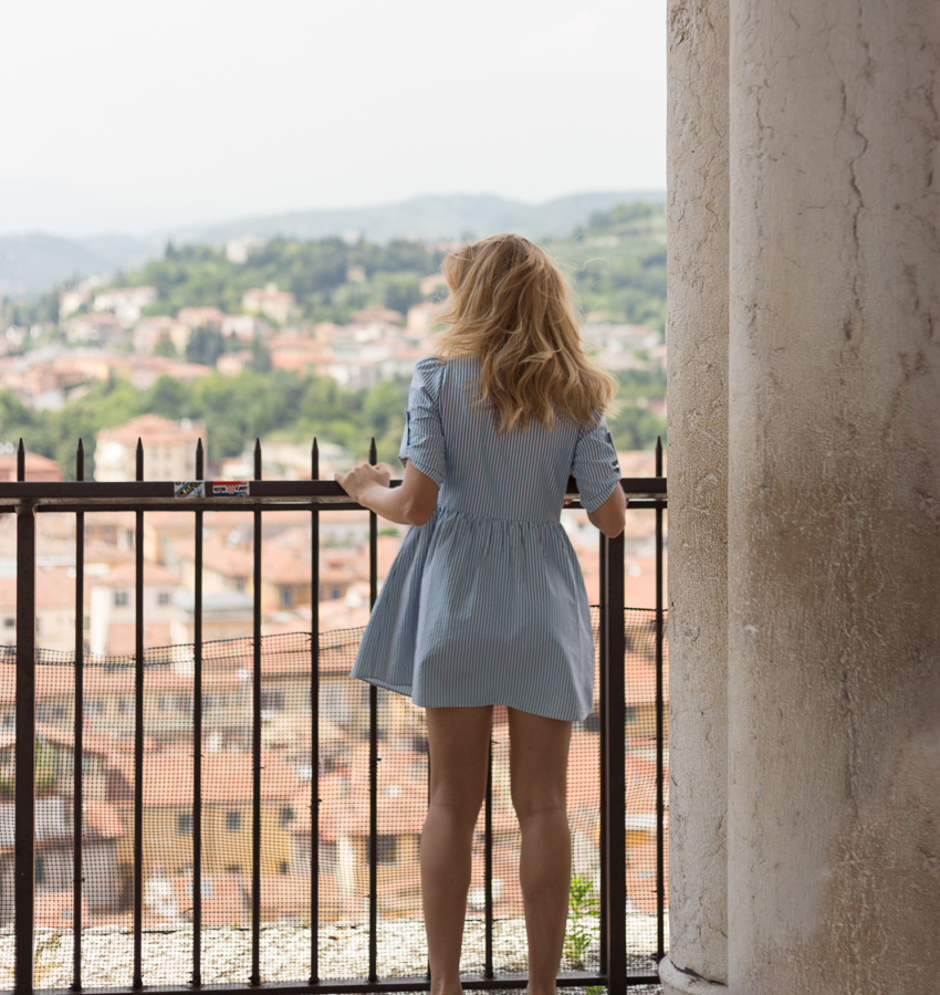 A young woman views Verona from the tower lookout.